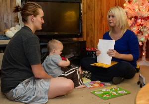 Courtney Trent, right, of Save the Children, visits with Britny Hurley, left, and her 19-month-old son, Landon, in Jackson, Ky. Credit Jonathan Palmer for The New York Times